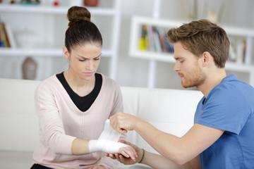 Man bandaging girlfriend's wrist