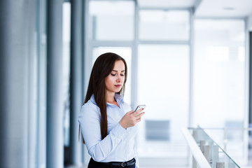 Serious attractive woman standing in modern interior and typing on phone