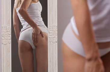 Woman checking cellulite in front of mirror, close up of beautiful female body legs. Healthy nutrition and weight losing concept
