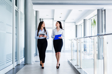 Two attractive womens walking trought modern interior and talking about work
