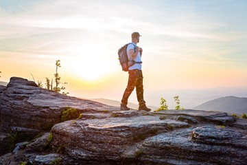 Man tourist on top of hill at sunrise.