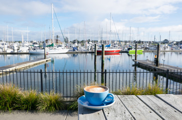 Fotobehang Nieuw Zeeland Cup of flat white coffee at Marsden Cove Marina, Whangarei, New Zealand, NZ