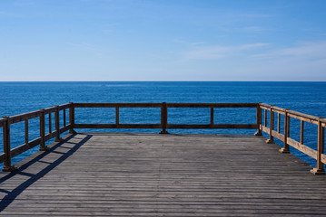 Wooden pier in blue ocean with horizon background. Place for advertising travel, fishing, diving, shipping products. Perfect field with sea, free sky, fresh air.