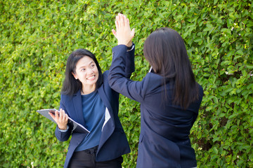 Businesswoman two people high fiving outdoors nature background.