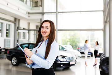 Attractive business woman standing in modern car dealership with some papers in her hands