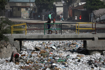 People walk on a bridge over a canal covered in garbage in Port-au-Prince