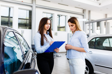 Two women makeing a agreement in modern car dealership