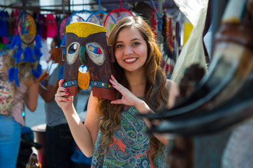 Close up of a young smiling beautiful woman holding in her hands a mask made of wood, in a store background