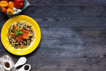 Delicious pasta with fresh vegetables and cheese, on a wooden background .