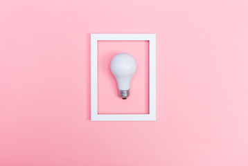 Colored lightbulb on a pink background