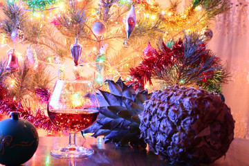 Beautiful toys on the branches of a festively decorated Christmas tree and a glass of drink on the table