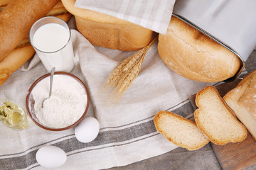 Different bread loaves and ingredients on table