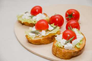 Italian bruschetta with soft cheese, tomatoes, rosemary and fresh salad on the plate. Space for text