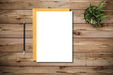Top view of blank paper page on wood background office desk with black pencil. Minimal flat lay style