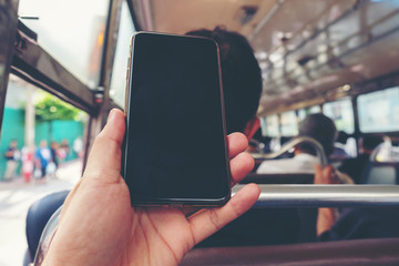 Close up view on the hands of a young hand man show mobile phone or smsrtphone blank screen,  Using cellphone inside bus, background as technology and travel concept.