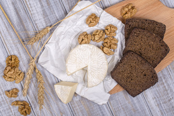 Brie type of cheese. Camembert cheese. Fresh Brie cheese and a slice on a wooden board with walnuts and black bread slice. Italian, French cheese.