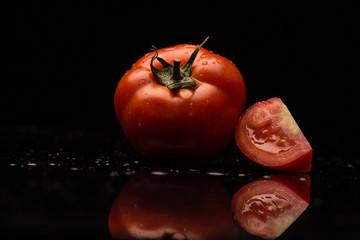 Fresh red tomato on a black background