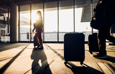 Poster Airport Silhouette of woman walking with luggage walking at airport terminal window at sunrise time,travel concept,journey lifestyle