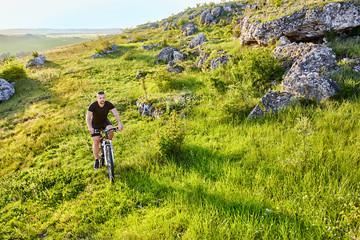 Attractive cyclist riding the bike on summer trail near beautiful big rocks.