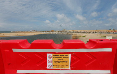 """A danger sign is seen on a plastic barrier in front of the land reclamation at """"Colombo Port City"""" construction site in Colombo"""
