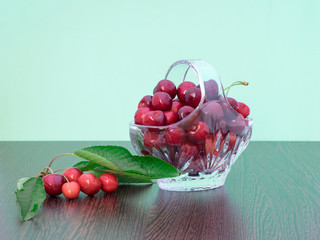 Freshly picked cherries in a crystal basket, on a green background, with a branch of cherry tree with leaves and cherries still on