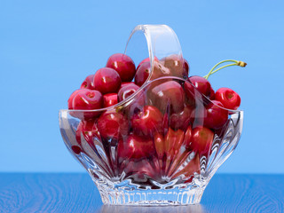 Freshly picked cherries in a crystal basket on a blue background
