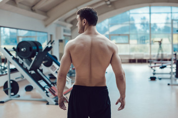 Sexy muscular man in gym working out. Strong male naked torso.