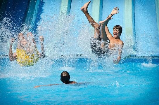 Young people having fun on water slides in aqua park, splashing into swimming pool