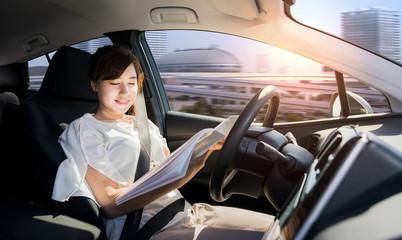 young woman reading a magazine in autonomous car. self driving vehicle. autopilot. automotive technology.