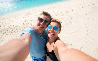 beautiful happy smiling couple making selfie on a beach, front view