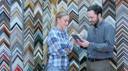Male customer showing picture to seller using digital tablet, looking for a frame in store