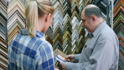 Senior man worker helping young female customer to pick up frame for a picture in atelier