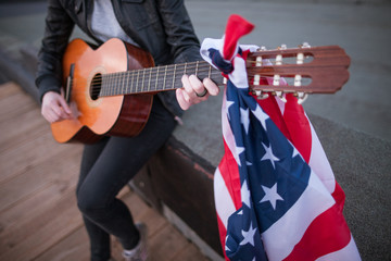 Artist with the US flag playing the guitar. Acoustic concert on the roof. Unrecognizable teenager on vacation at a party on Independence Day
