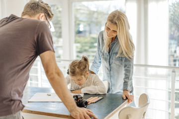 Mature woman and man looking at girl drawing at home