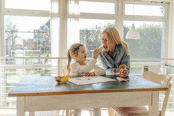 Mature woman and girl at home at the table eating and drawing