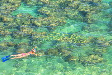 Woman snorkeling over coral reef in famous Hanauma Bay Nature Preserve, Oahu island, Hawaii, USA. Female snorkeler swims in tropical sea with american flag bikini. Watersport activity in Hawaii.