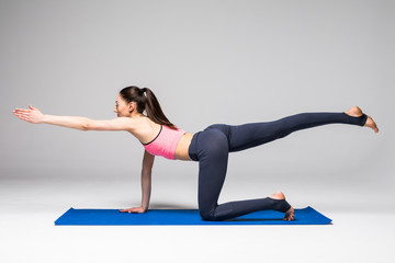 Young attractive woman practicing yoga, standing in different yoga exercise, wearing sportswear isolated on grey background. Series of Yoga position concept