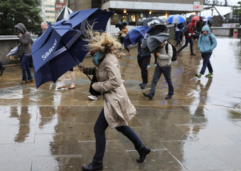 A woman struggles with her umbrella on a wet and windy morning on London Bridge, in London