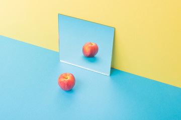 Apple on blue table isolated over yellow background near mirror