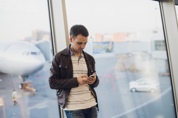 Young business man in airport using smartphone .