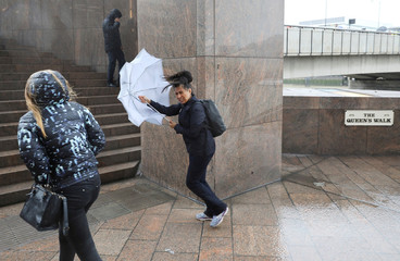 A woman struggles with her umbrella as she walks towards London Bridge on a wet and windy morning in London
