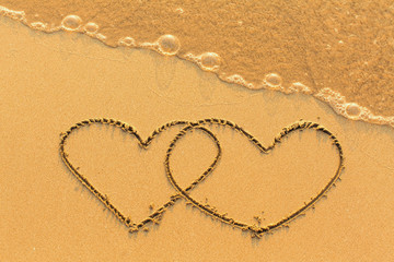 Two hearts drawn in the sea sand with the soft wave.