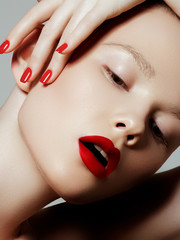 Beautiful woman with red matte lipstick. Beautiful woman face. Makeup detail. Beauty girl with perfect skin. Red lips and nails manicure