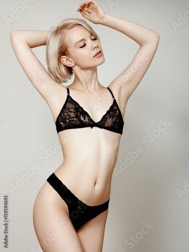 4f66da97a Vivacious sexy young blonde woman with a beautiful smile posing in a black  lingerie isolated studio portrait