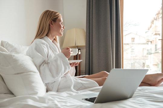Young pretty woman in bathrobe drinking coffee
