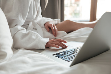 Cropped image of a woman in bathrobe on bed and using laptop