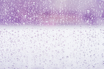 Rain drops and frozen water on window glass background, purple toning
