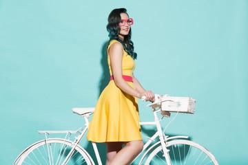 Beautiful woman in yellow dress on white bicycle.