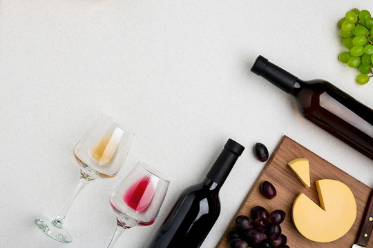 Two wine glasses with red and white wine,bottles of red wine and white wine, cheese on white background. Horizontal view from the top.