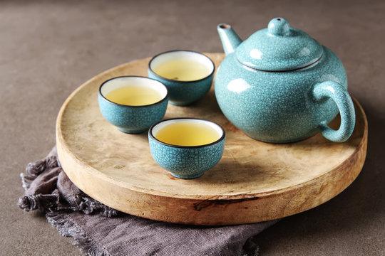 Porcelain chinese cups, steel teaspoon. Black, green, puerh, oolong, tieguanyin, sencha, tea. Gray background.